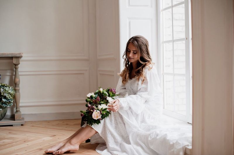 Bride Holding Bouquet While Sitting At Window Sill In Room