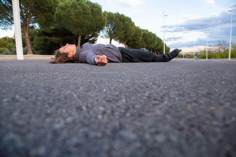 Man sleeping on road in city