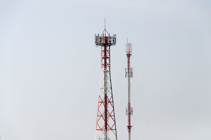 Low angle view of communication towers against clear sky