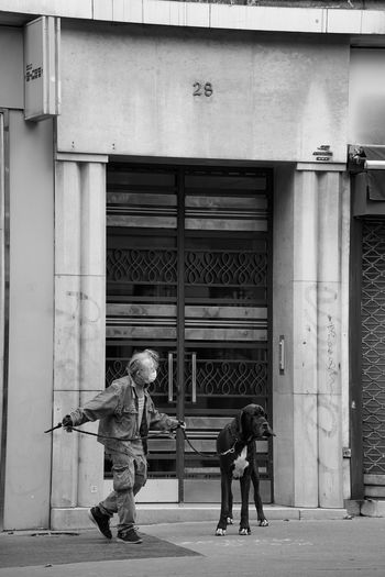 Side view of man and woman walking on street against building