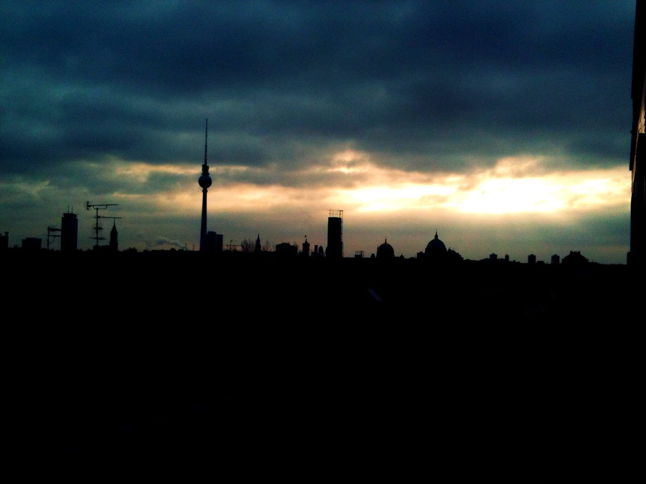 Silhouette city against cloudy sky