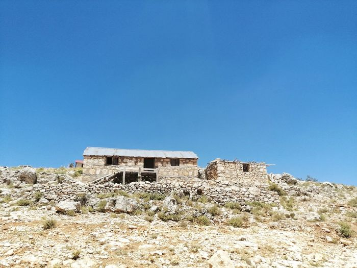 Low angle view of abandoned building against clear blue sky