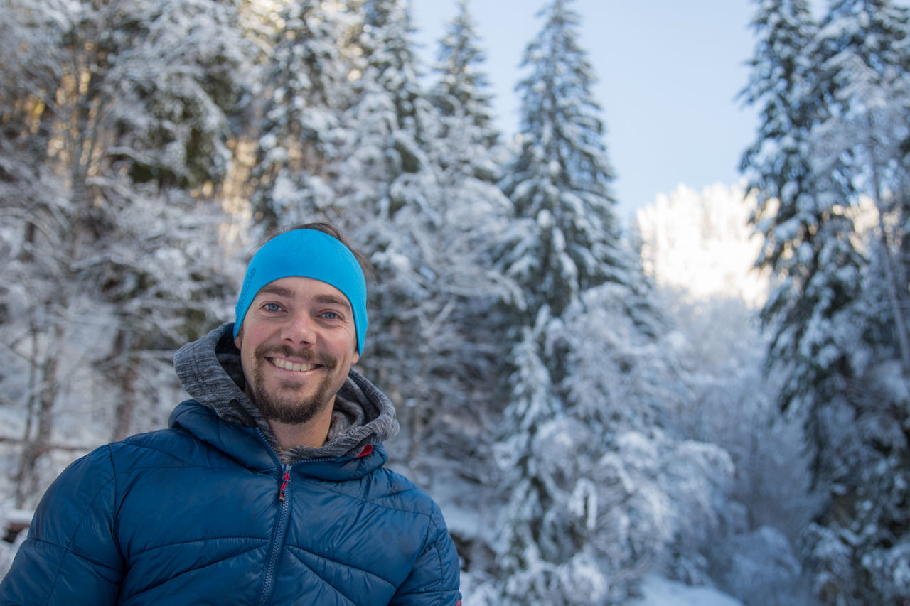 PORTRAIT OF SMILING MAN IN SNOW AGAINST MOUNTAINS