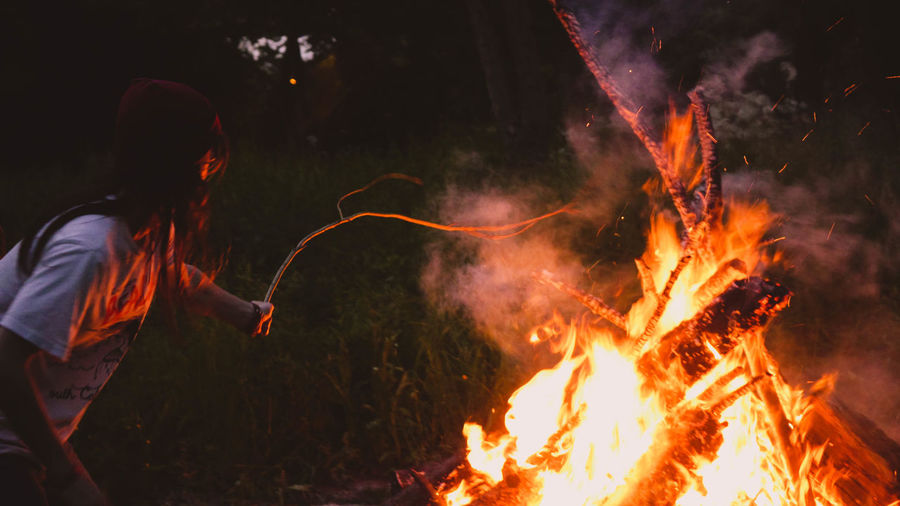 Side view of woman burning sticks in forest