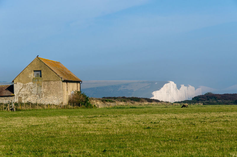 Farm building at seaford head, south downs, against distant seven sisters white cliffs, east sussex