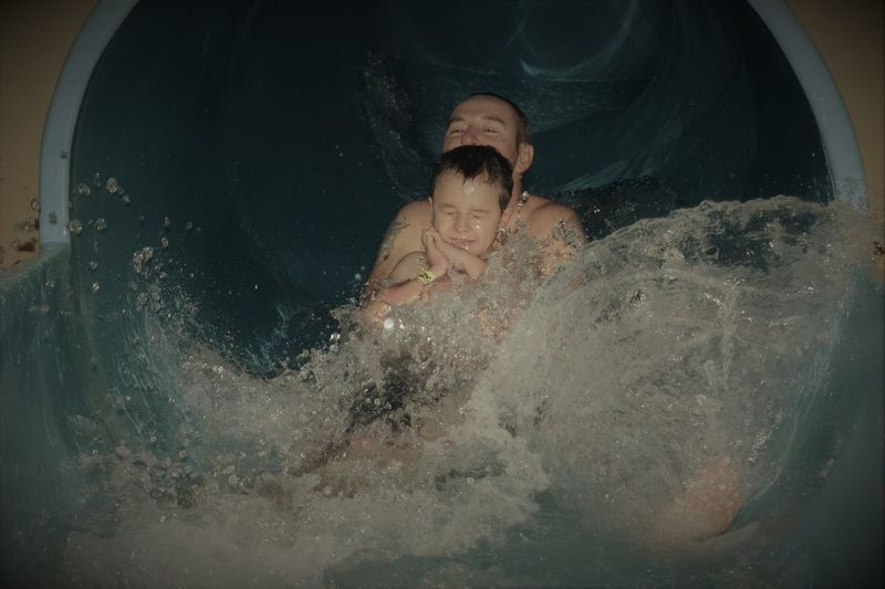 Shirtless Man With Son Sliding In Water Slide