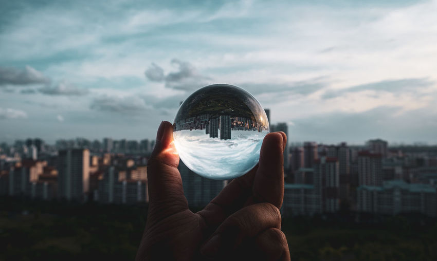 Person holding lens ball against cityscape