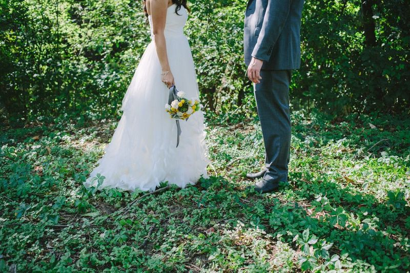 Low section of bride and groom standing on field
