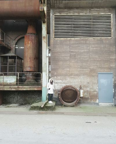 Blending in or when people match places Built Structure Abandoned Building Exterior Technology Architecture Old Buildings Door Light Colors Heart Love Adapted To The City Rusty Faded Industry Steelwork Factory Pipeline Facades Vintage One Person Female Model Coat Lines Steel When People Match Places