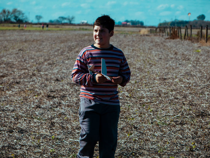 Boy with toy airplane walking on land