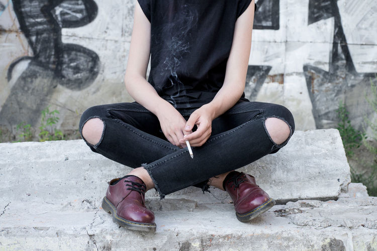 Low Section Of Woman Sitting By Concrete Wall