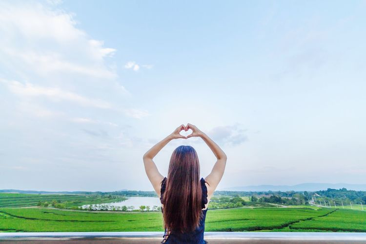 Rear view of woman making heart shape against land