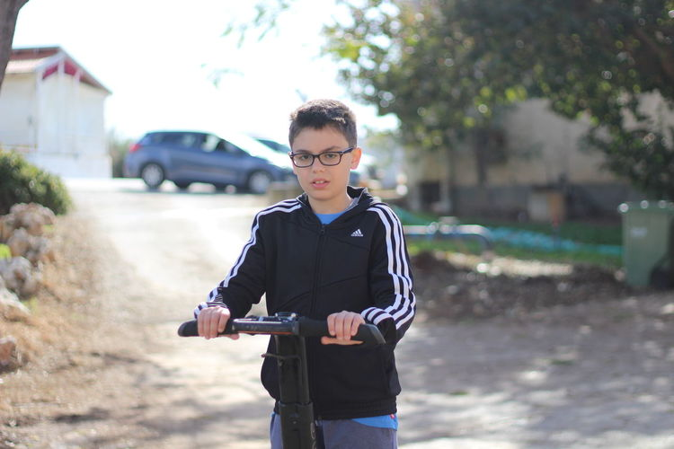 Portrait of boy with push scooter standing on road
