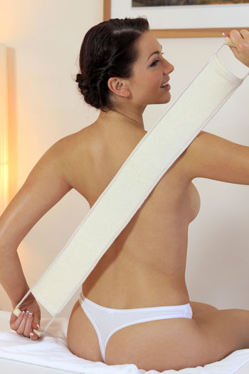 Rear View Of Smiling Young Woman Sitting At Massage Table At Health Spa