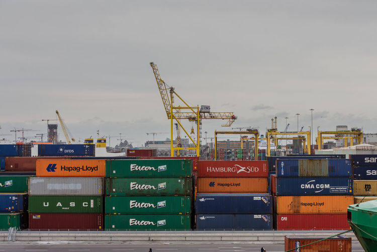 Stack of cargo containers at harbor against sky