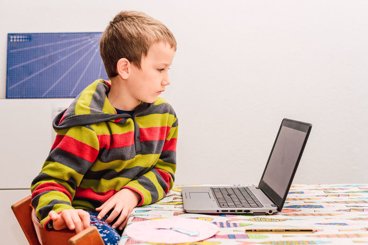 Full length of boy sitting on mobile phone