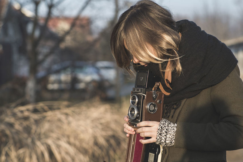 Analogue Photography Camera Camera - Photographic Equipment Day Field Focus On Foreground Holding Leisure Activity Lifestyles Nature One Person Outdoors Photographer Photographing Photography Themes Real People Rear View SLR Camera Standing Technology Tree Weapon Women Young Adult Young Women