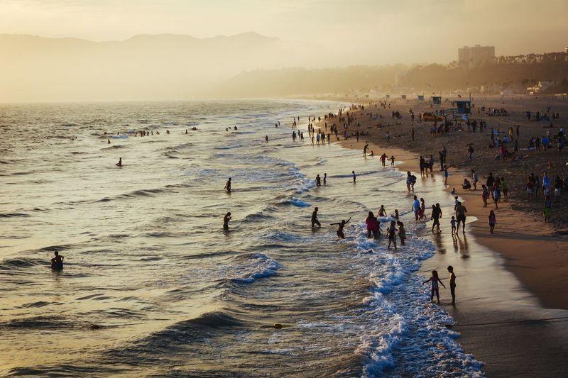 People Enjoying Summer Sunset At Beach