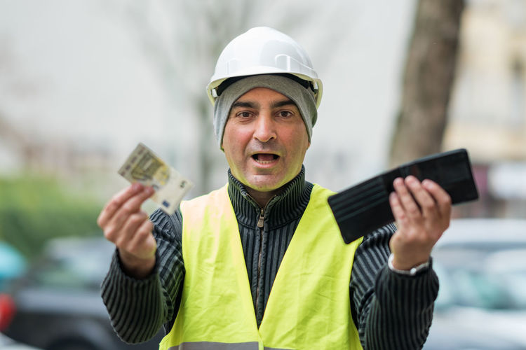 Portrait of engineer in reflective clothing holding currency and wallet