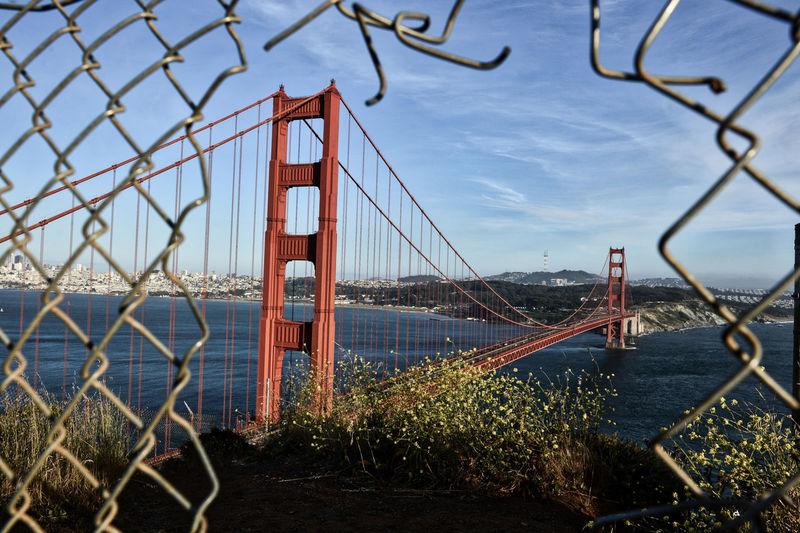 View of bridge through chainlink fence