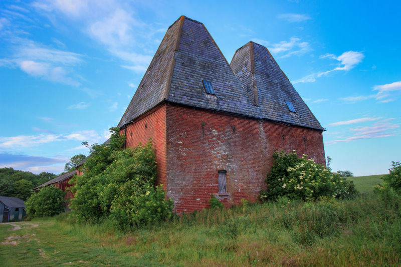 Oast House, Garden Of England, Kent, England. Architecture Sky Built Structure Nature No People Plant Hops Beer Brewing Iconic Buildings Vivid International Getty Images EyeEm Gallery Travel Destinations Tourism Sunrise Countryside Rural Scene History Grass Cloud - Sky Field Land Building Exterior Day Green Color Building Low Angle View Old Outdoors Tree The Past