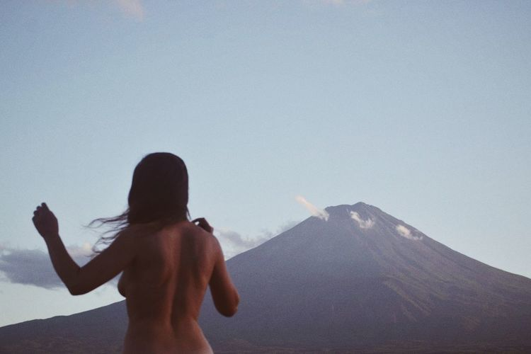 Rear view of shirtless woman standing against clear sky