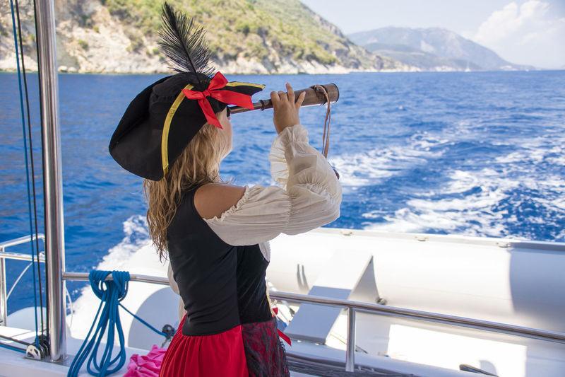 Woman looking through binoculars in boat on sea