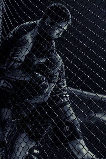 Portrait of woman in chainlink fence
