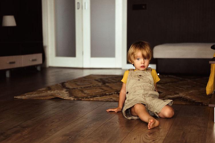 Cute baby girl sitting on hardwood floor at home