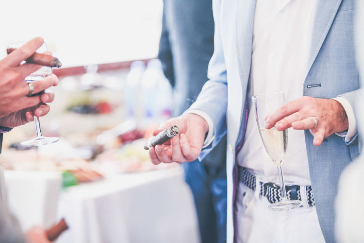 Businessman Cigar Close-up Day Holding Human Hand Indoors  Men Midsection Occupation People Real People Standing Togetherness Two People Well-dressed Wine Working