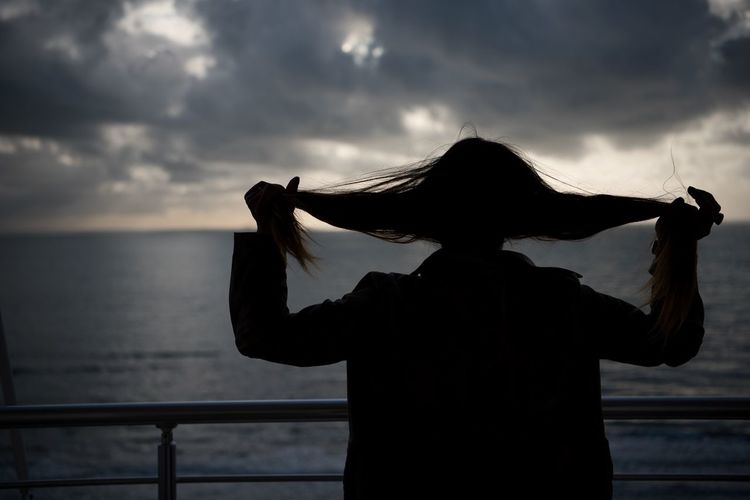 Rear View Of Silhouette Woman Holding Her Hair While Standing By Sea Against Cloudy Sky