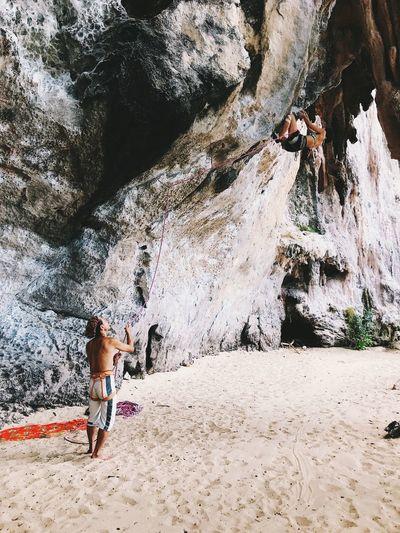 Man looking at woman climbing rock at beach