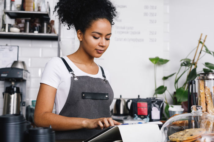 African American Coffee Shop Females Horizontal Young Barista Businesswoman Cafe Checkout Indoors  Mixed Race Occupation One Person Owner Payment Real People Self Employed Small Business Technology Wireless Technology Working Business Stories