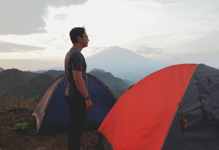 Man Standing By Tent On Mountain Against Sky