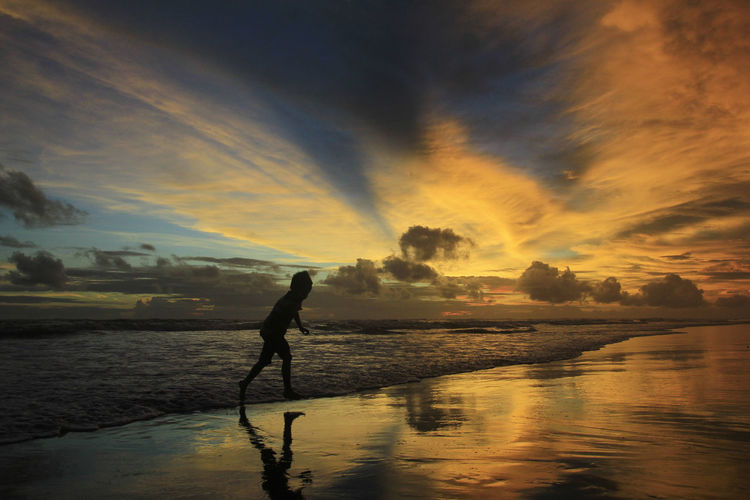 Yogyakarta-Indonesia, 18/04/2018: Silhouette of a boy running to avoid the Parangtritis beach waves at dusk with a dramatic sky burning. Leisure Activity Outdoors Land Nature Scenics - Nature Beauty In Nature Real People Sunset One Person Sky Water Cloud - Sky Silhouette Reflection Sea Beach Full Length Lifestyles Men Sunset Silhouettes Sunset #sun #clouds #skylovers #sky #nature #beautifulinnature #naturalbeauty #photography #landscape Waves, Ocean, Nature Ocean View Seascape Tourist Attraction