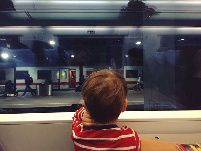 Rear View Of Boy Looking Through Train Window