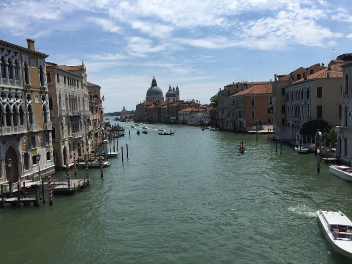 Grand canal amidst buildings against sky on sunny day