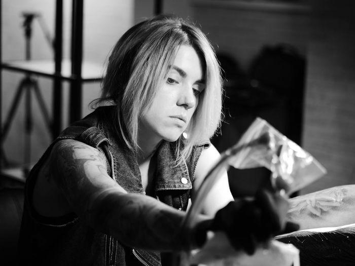 Artist making tattoo on man at studio