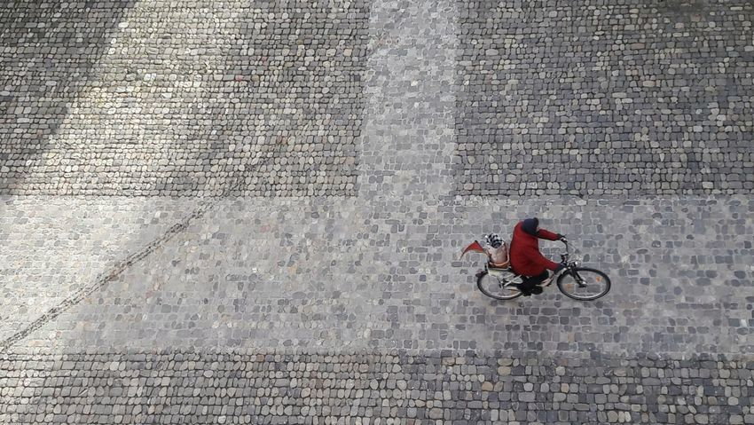 The last, for the moment ;-)) Bicycle Transportation Cycling Paving Stones Place Woman On Bike Red Flying High Minimalism Architecture High Angle View Pattern The Street Photographer - 2017 EyeEm Awards