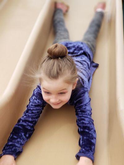 High angle view of playful girl lying on slide