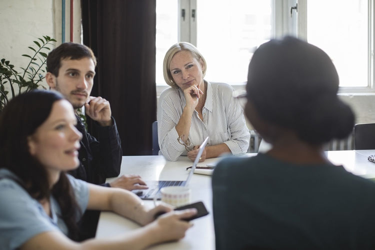 Entrepreneurs listening to female colleague during meeting in board room