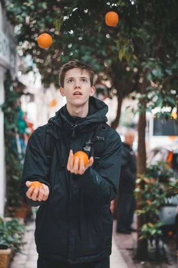 Juggle Struggle Zirkus Circus Oranges Jonglage Juggle Juggling One Person Real People Front View Standing Lifestyles Orange Color Focus On Foreground Leisure Activity Waist Up Outdoors Holding Fruit Winter Plant Orange Men Tree Food Portrait The Art Of Street Photography