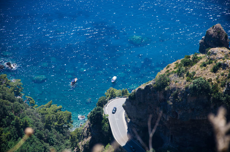 Amalfi coast - detail of hairpin bend, cliff, turquoise sea and boats. view from path of gods.