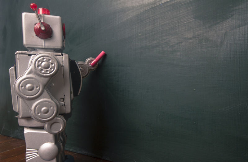Close-up of robot writing on wall