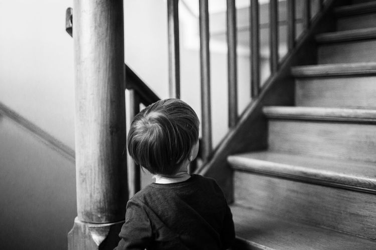 Rear view of boy by standing by staircase at home