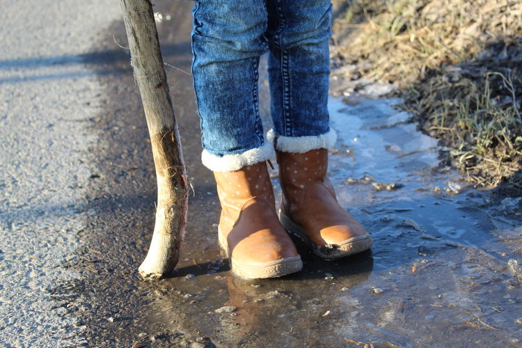 Low Section Of Girl Standing On Puddle