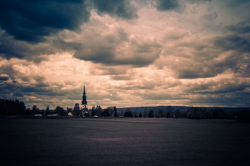 Distant view of stora tuna church on field against cloudy sky at dusk