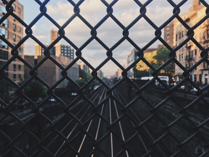 Railroad tracks seen through chainlink fence in city