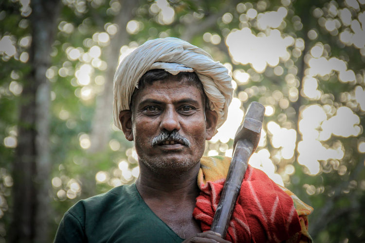 Portrait of senior man holding axe in forest