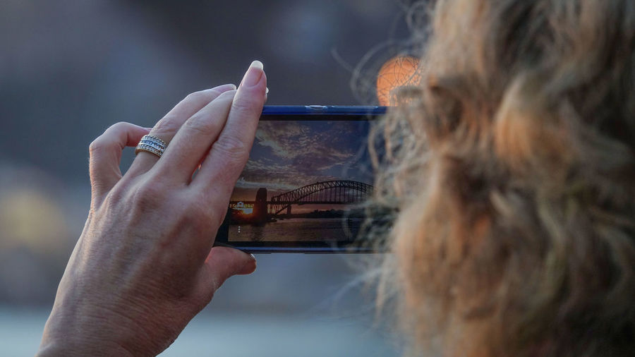Close-up of woman photographing sydney harbour bridge with smart phone